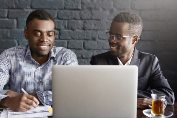 people-business-teamwork-cooperation-concept-two-african-american-corporate-workers-formal-clothing-working-together-common-presentation-generic-laptop-computer-modern-office_273609-321